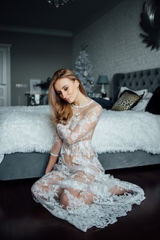 A girl in a lace dress on a bed