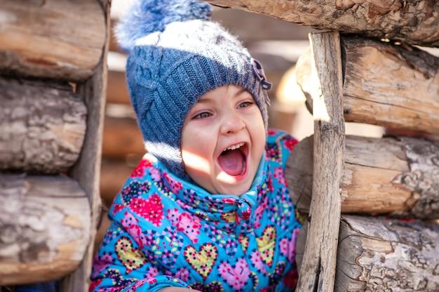 Девушка смеется и играет в деревянном доме