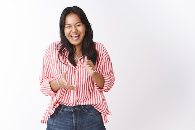 Girl laughing over hilarious joke applausing and giggling from fun and joy. portrait of carefree attractive young woman in striped blouse chuckling and clapping hands during stand-up comedy show
