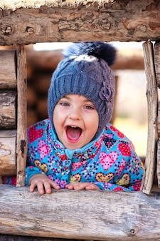 Girl laughing and playing in a wooden house