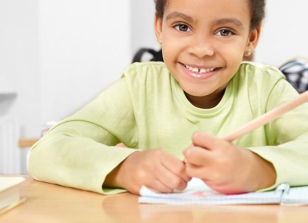 学校で学びながら笑っている女の子