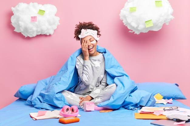 Девушка счастливо смеется, делает лицо ладонь носит мягкую пижаму и с завязанными глазами работает дистанционно в карантинных позах с бумагами липкие заметки на кровати остается дома одна
