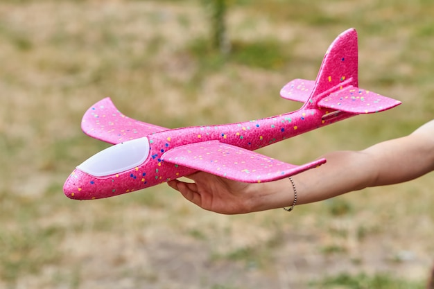Girl launching a pink toy plane into the air