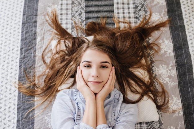 The girl laying in her pajamas on the bed in her room. stylish gray-white interior.