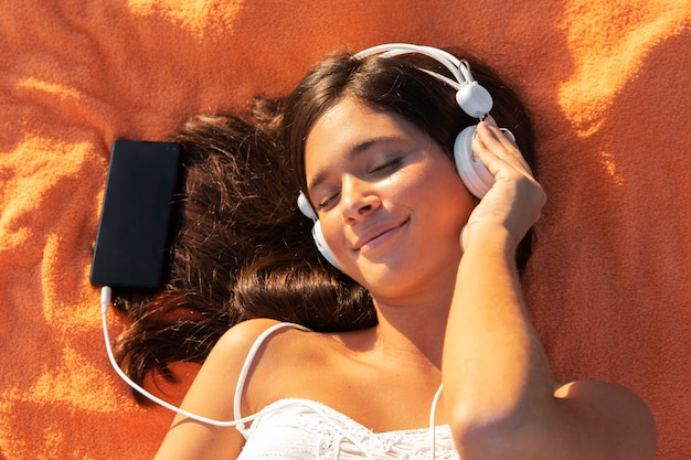 Девушка лежит на ткани с наушниками
