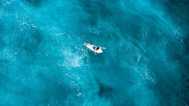 Ragazza che pone su una tavola da surf e che galleggia nel mare aperto con acqua cristallina in maldive