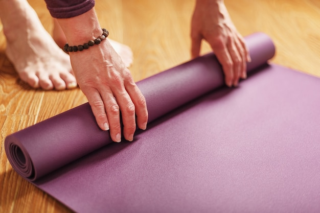 A girl lays out a lilac yoga mat before a workout practice at home on a wooden floor.