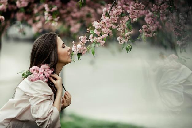 Девушка склоняется нюхает сакуры в парке