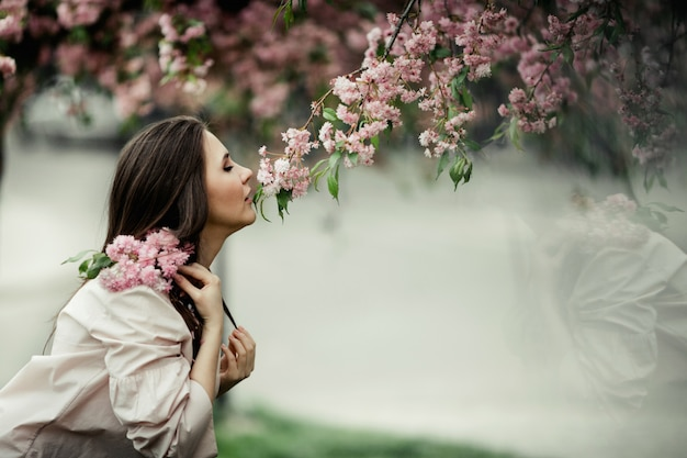 Girl leaning sniffs a sakura in the park
