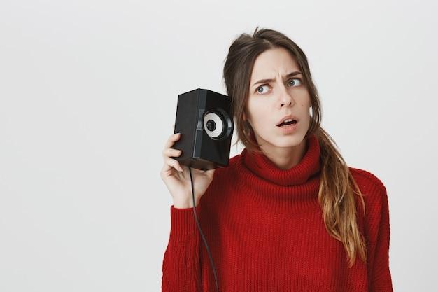 Girl leaning to speaker, listen to sound carefully