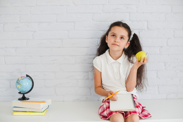 Girl leaning on wall holding apple thinking