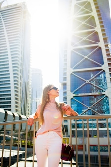 Girl leans her elbows on handrails posing before blue skyscrapers in dubai