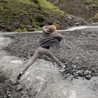 Girl leaping over fast flowing stream with rocky riverbank