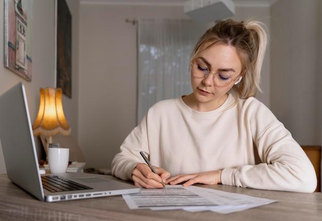Девушка изучает английский онлайн на своем ноутбуке Premium Фотографии