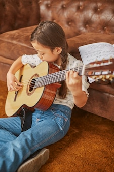 Girl learning how to play guitar at home