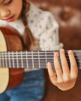 Девушка учится играть на гитаре дома