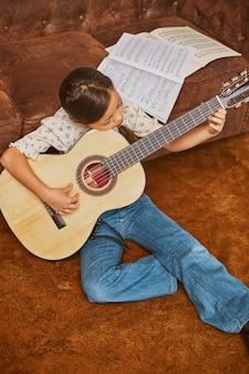 집에서 기타를 연주하는 방법을 배우는 소녀