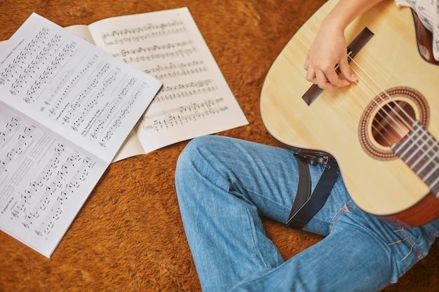 家でギターを弾く方法を学ぶ女の子
