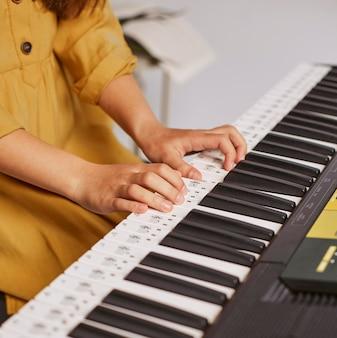 Девушка учится играть на электронной клавиатуре