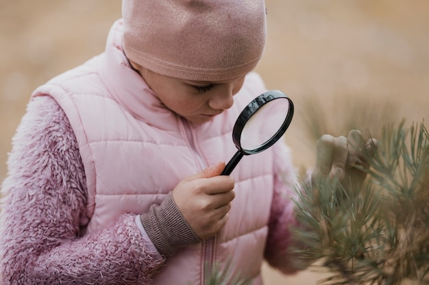 Girl learning science in the nature with a magnifier