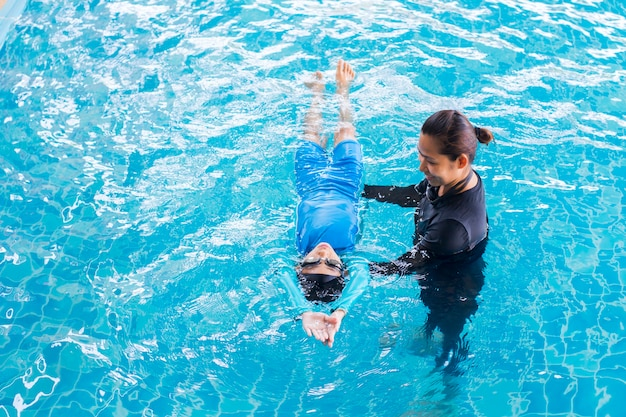Girl learning to swim with coach at swimming pool