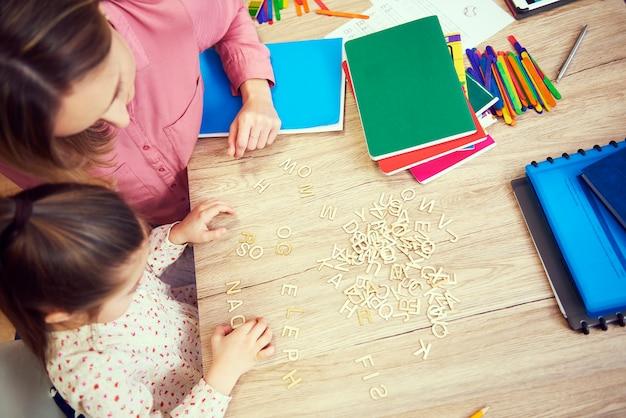 家でアルファベットを学ぶ女の子