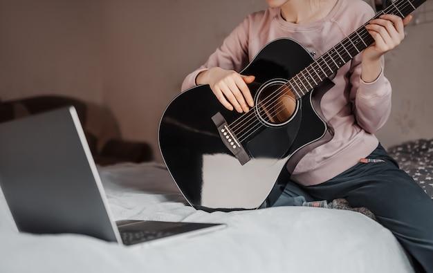 Девушка учится играть на гитаре с помощью онлайн-обучения дома