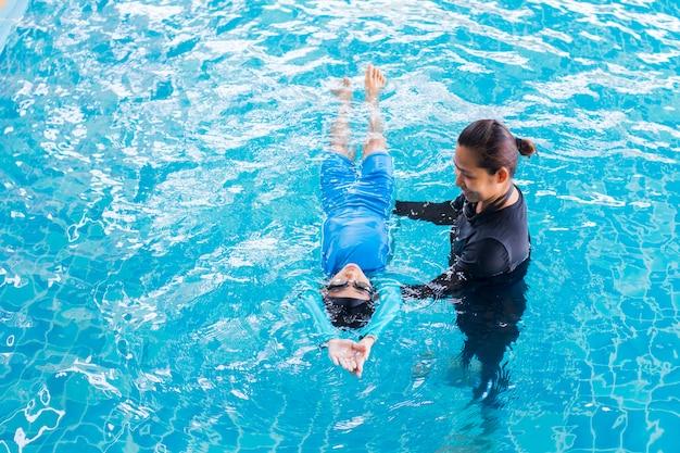 スイミングプールでコーチと一緒に泳ぐことを学ぶ女の子
