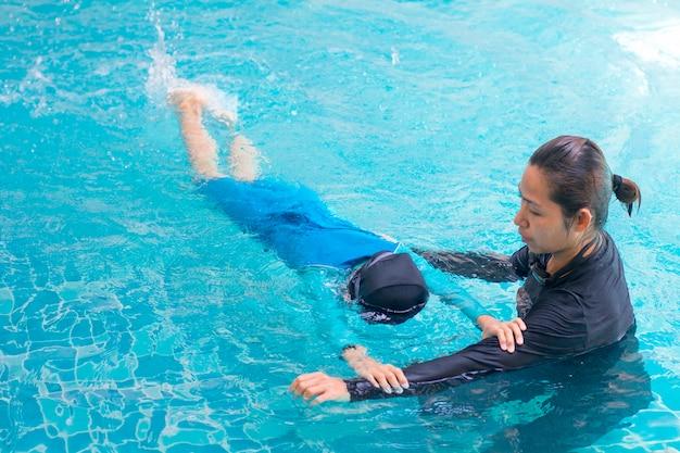 レジャーセンターでコーチと泳ぐことを学ぶ女の子