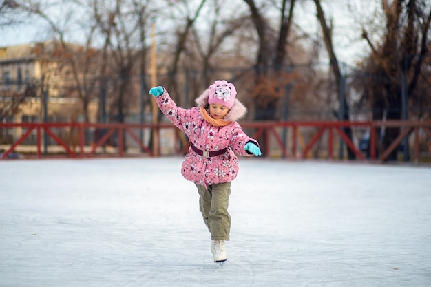Girl learns to skate on an ice rink on a street in winter