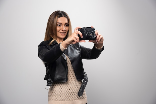 Girl in leather jacket checking her photo history on the camera.