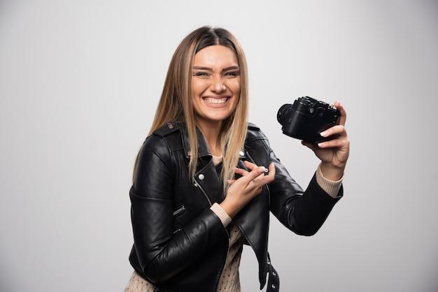 Ragazza in giacca di pelle che controlla la sua cronologia fotografica sulla fotocamera