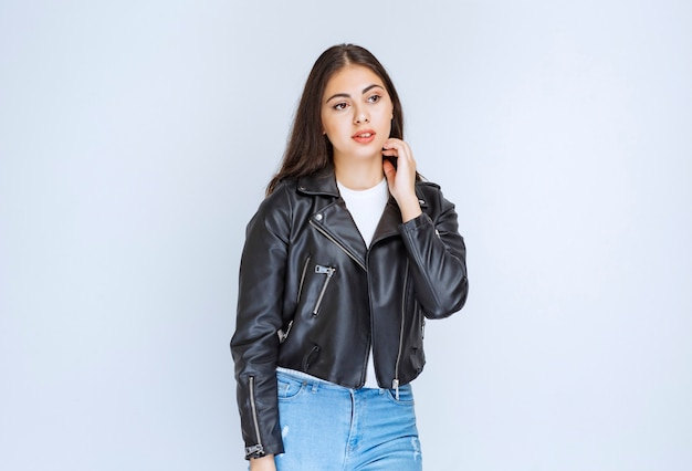 Girl in leather jacket giving neutral and relaxed poses.