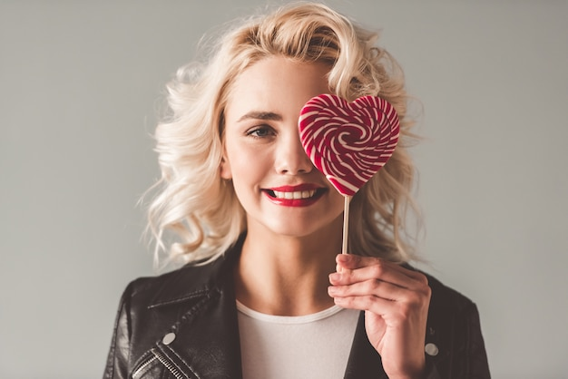 Girl in leather jacket is holding a heart shaped lollipop