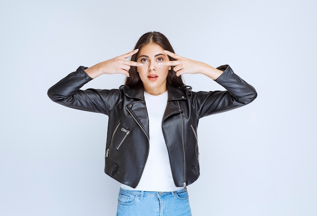 Girl in leather jacket looking across her peace signed fingers.