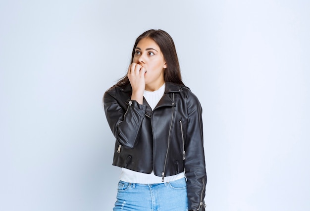 Girl in leather jacket looks scared and terrified.