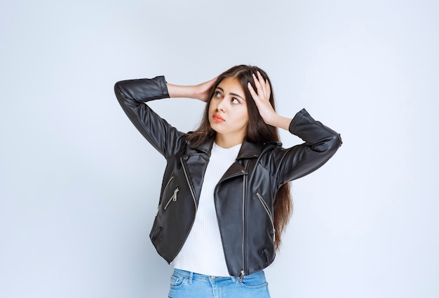 Girl in leather jacket looks tired and exhausted.