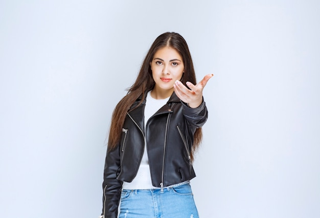 Girl in leather jacket presenting someone aside.