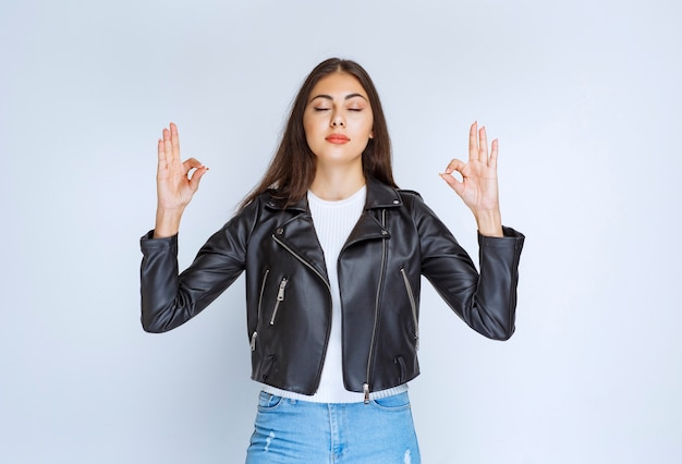 Girl in leather jacket showing enjoyment sign.