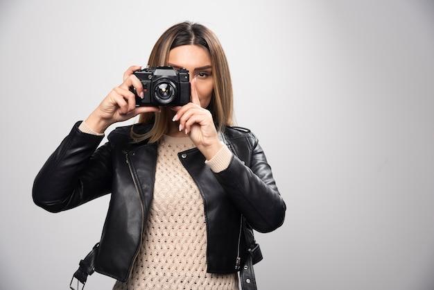 Ragazza in giacca di pelle, scattando le sue foto in posizioni eleganti e positive.