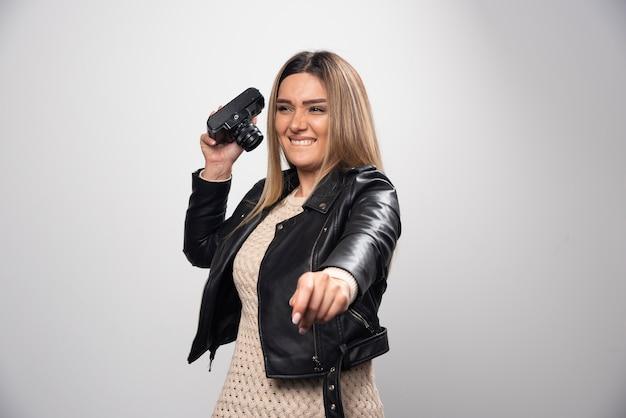 Ragazza in giacca di pelle che scatta le sue foto in posizioni strane e divertenti.
