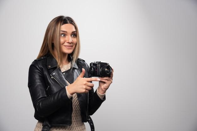 Ragazza in giacca di pelle che scatta le foto in posizioni strane e divertenti