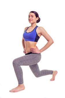 Girl in leggings and a top is warming up.