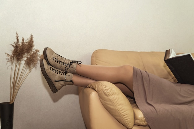 A girl legs in the boots on a couch with an open book, next to a vase on the floor with dried reeds. relaxing concept.