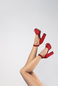 Girl legs wearing red high heels isolated on white