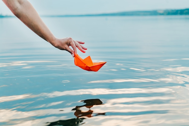 The girl lets down her paper boat to the water with her hand. an orange ship is hanging over the river