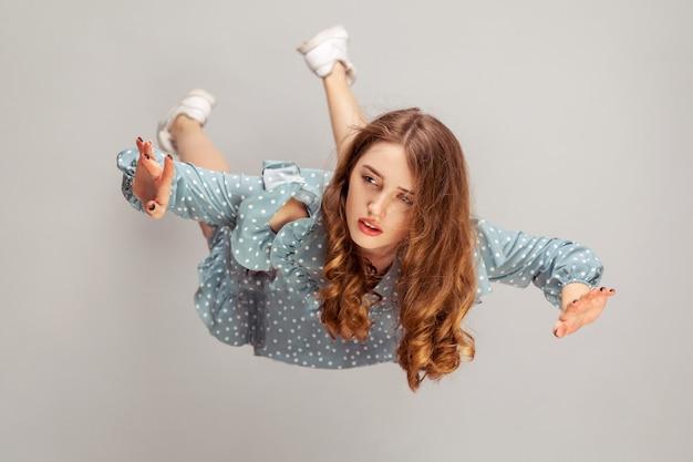 Девушка парит в воздухе с мечтательным мирным выражением лица