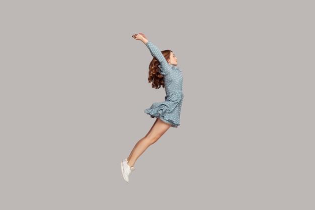 Девушка парит в воздухе с поднятыми руками, модель смотрит в сторону, сосредоточенно, сосредоточенно,