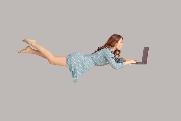 Девушка парит с ноутбуком, читая шокирующее новостное сообщение на компьютере во время полета в воздухе