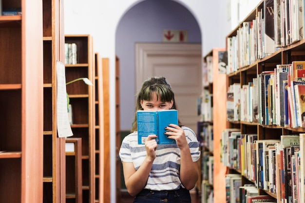 Girl in library hiding face behind a book